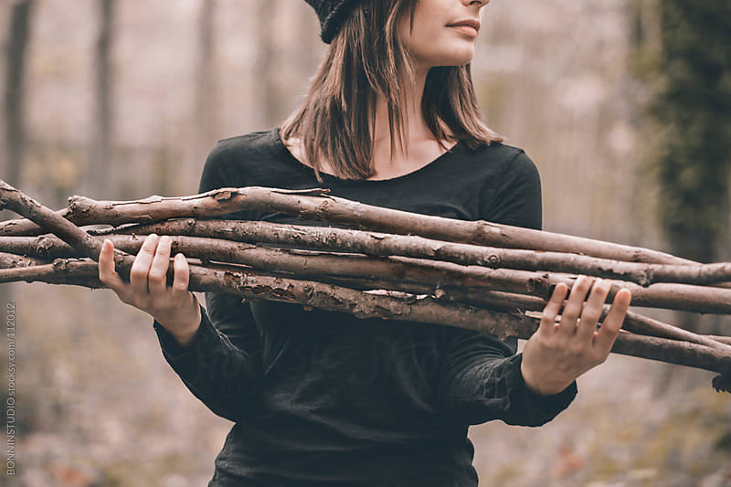 Woman collecting wood for winter on poplar forest. She is holding branches. by BONNINSTUDIO for Stocksy United