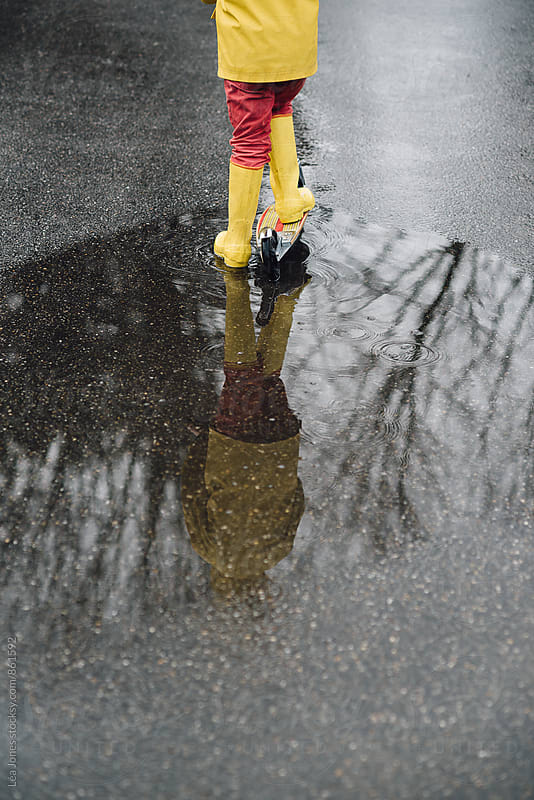 child standing on a scooter by a puddle by Léa Jones for Stocksy United