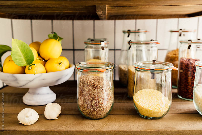 Pantry full of different spices in glass jars by Trent Lanz for Stocksy United