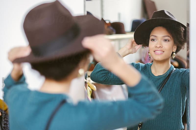 Beautiful Woman Trying Out a Hat in the Store by Aleksandra Jankovic for Stocksy United