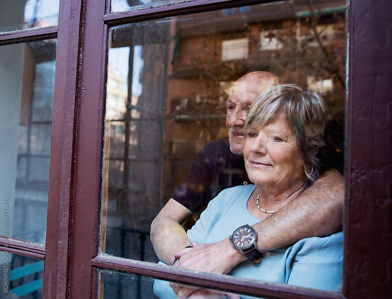 Elderly couple embracing looking through the window. by BONNINSTUDIO for Stocksy United