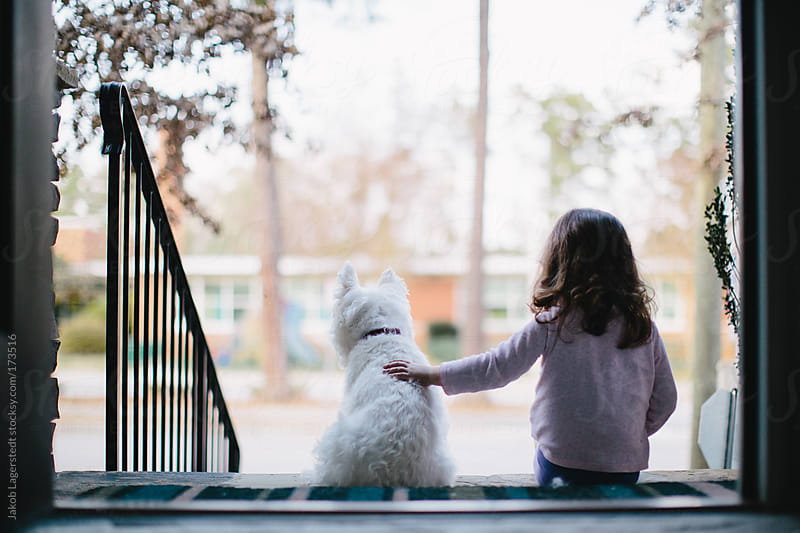 A toddler and a dog sitting in front of their home by Jakob for Stocksy United