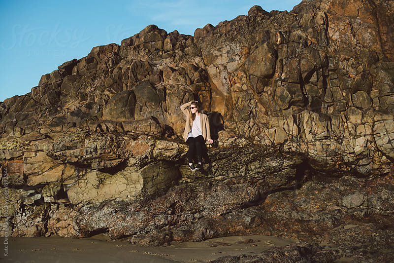 Young woman sitting on seaside rock ledge by Kate Daigneault for Stocksy United