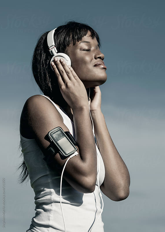 Woman Listening to Headphones with Digital Music Player by Stephen Morris for Stocksy United