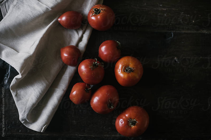 Tomato harvest on a dark wood table in natural light by Daring Wanderer for Stocksy United