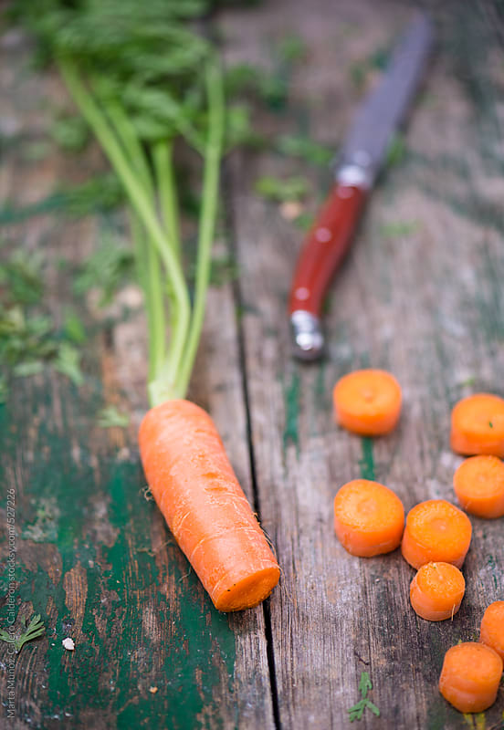 carrots and knife on vintage wooden surface by Marta Muñoz-Calero Calderon for Stocksy United