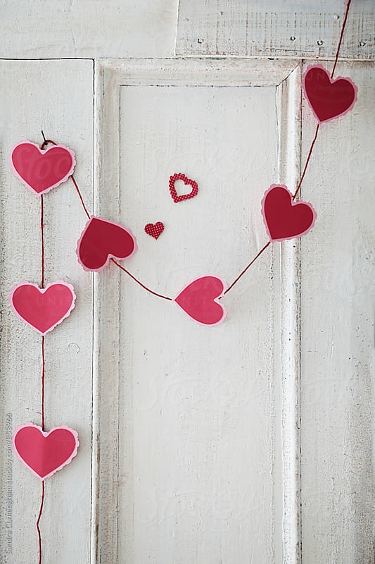 Garland of paper hearts on old door by Sandra Cunningham for Stocksy United
