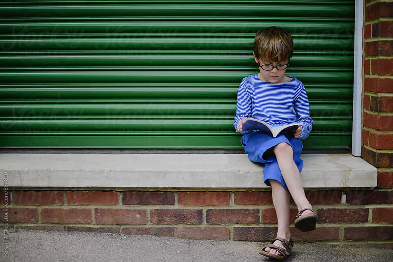 Boy wearing blue, reading a book  by Kirstin Mckee for Stocksy United