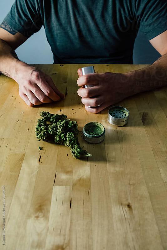 Caucasian male hands grinding marijuana by J Danielle Wehunt for Stocksy United