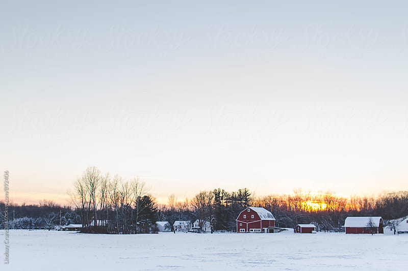 Snowy landscape with farm and red barn by Lindsay Crandall for Stocksy United