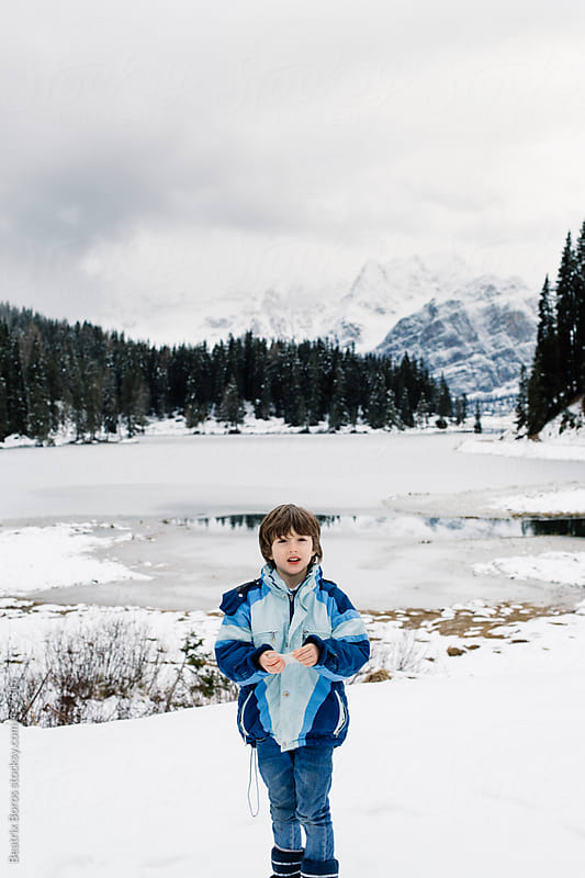 Boy holding a piece of ice and looking at camera in front of a frozen lake  by Beatrix Boros for Stocksy United