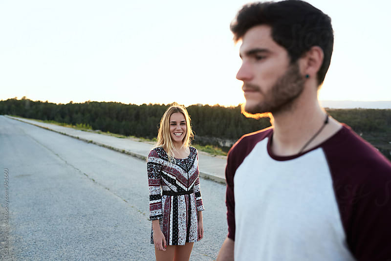 Beautiful smiling woman looking at her unfocused boyfriend by Guille Faingold for Stocksy United