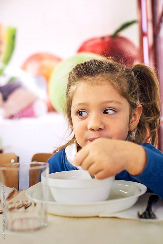Little Girl Having Breakfast at the School Canteen by VICTOR TORRES for Stocksy United