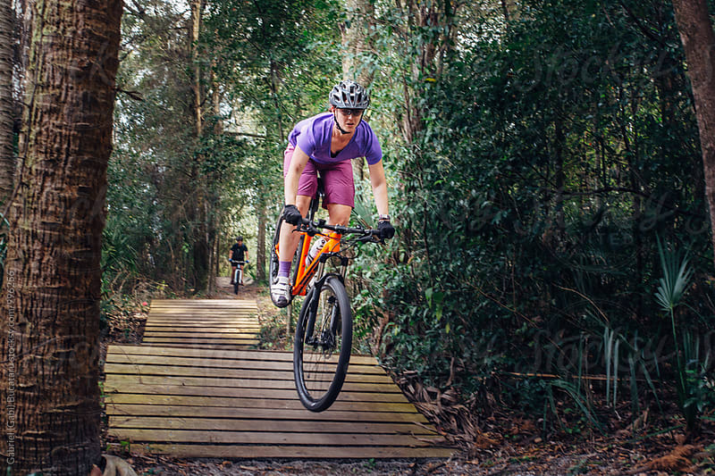 Female cyclist on a jump by Gabriel (Gabi) Bucataru for Stocksy United