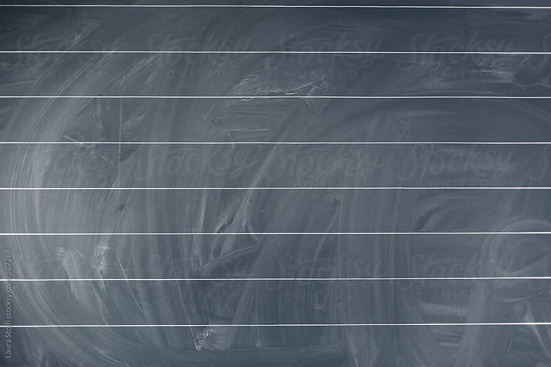 Blackboard with chalk marks and eraser passage signs on it by Laura Stolfi for Stocksy United