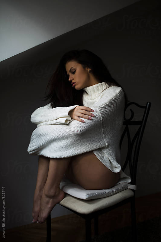 Attractive young woman sitting on a chair wearing long sweater by Jovana Rikalo for Stocksy United