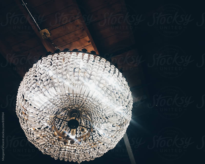 fancy chandelier hanging from a plain wood ceiling by Margaret Vincent for Stocksy United