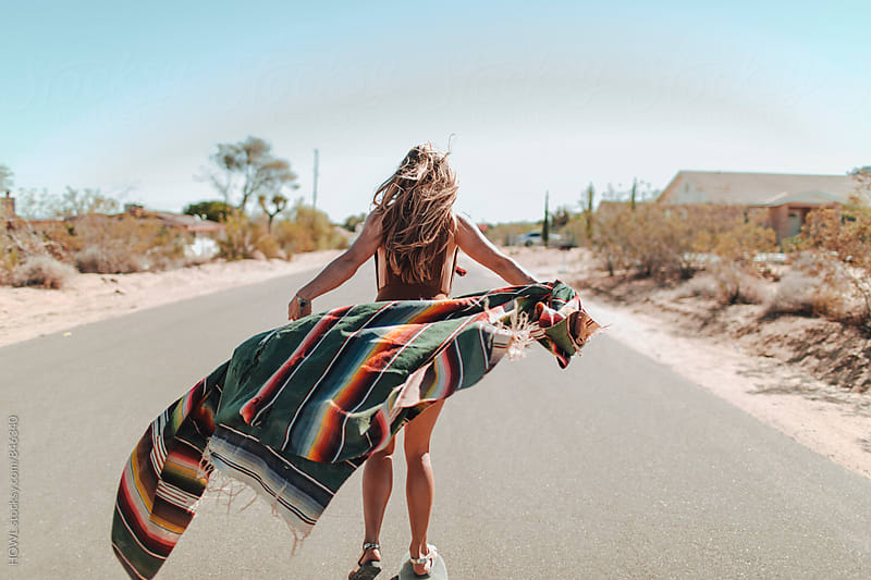 A carefree young woman stands in the middle of a desert road by HOWL for Stocksy United