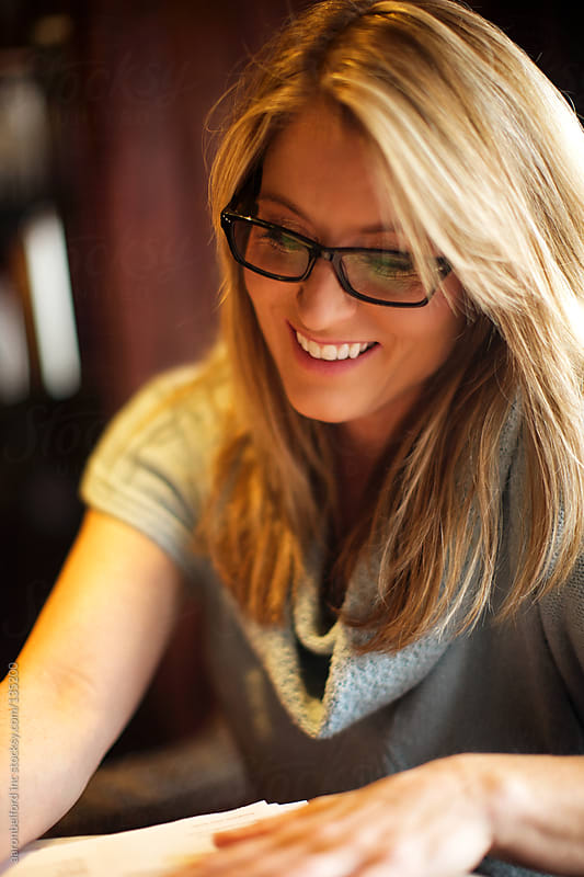 Woman smiles while she fills out paperwork by aaronbelford inc for Stocksy United