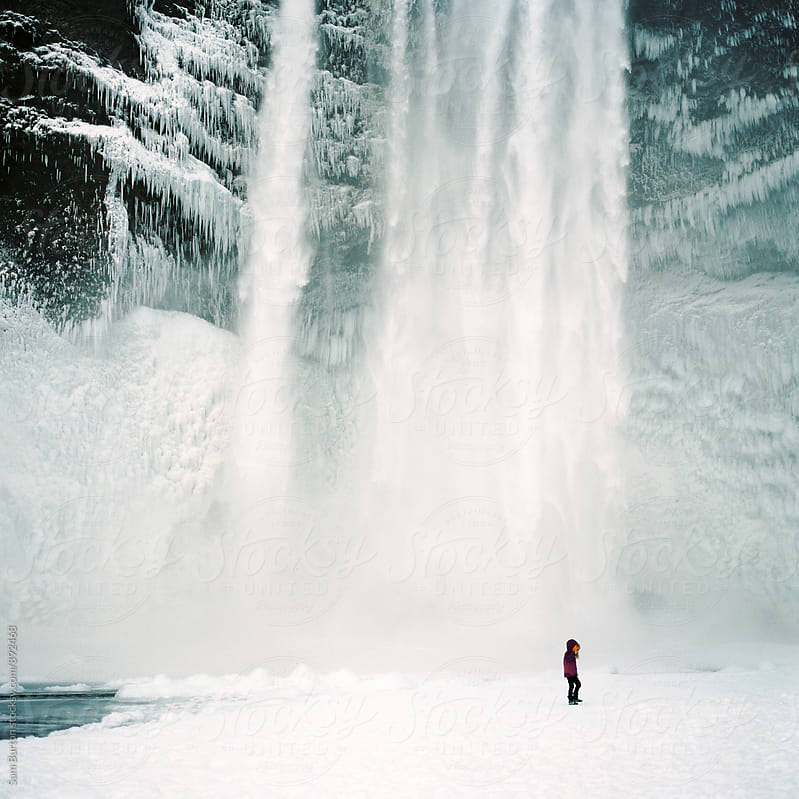 Small child standing in from of skogafoss waterfall by Sam Burton for Stocksy United