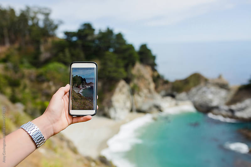 Young man taking a cellphone photo of McWay Falls  by Amy Covington for Stocksy United