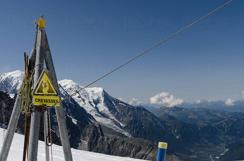 Crevasse warning sign in the mountains by Neil Warburton for Stocksy United