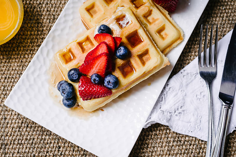 waffles on a plate with juice and cutlery by Gillian Vann for Stocksy United