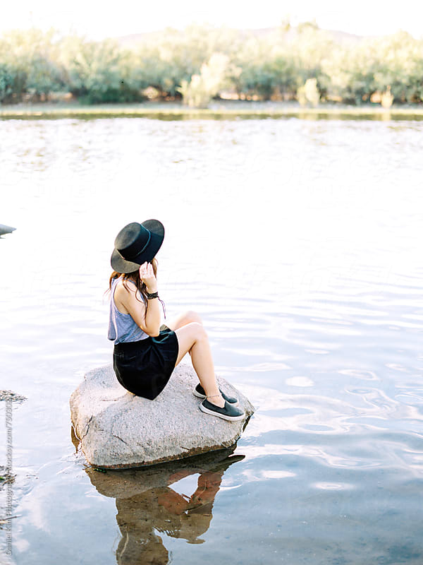 Young woman sitting on rock in water by Daniel Kim Photography for Stocksy United