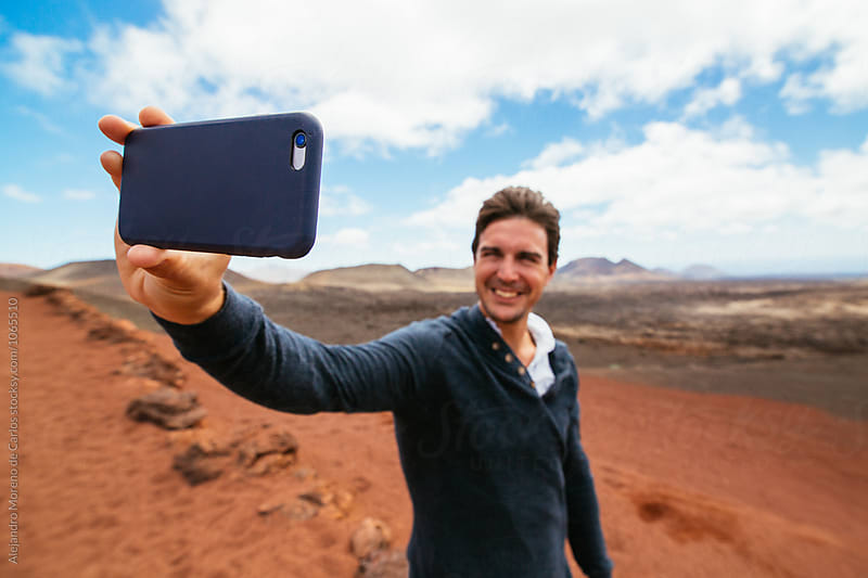 Cheerful man taking selfie against of mountains by Alejandro Moreno de Carlos for Stocksy United