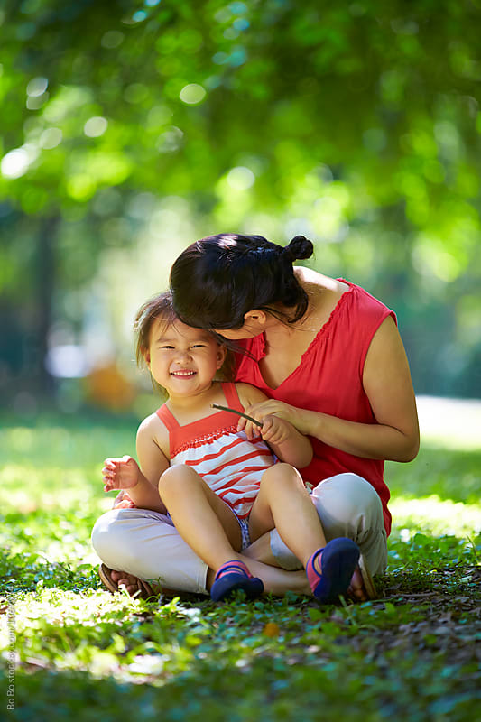 little girl sitting on her mother's leg outdoor in the park by Bo Bo for Stocksy United