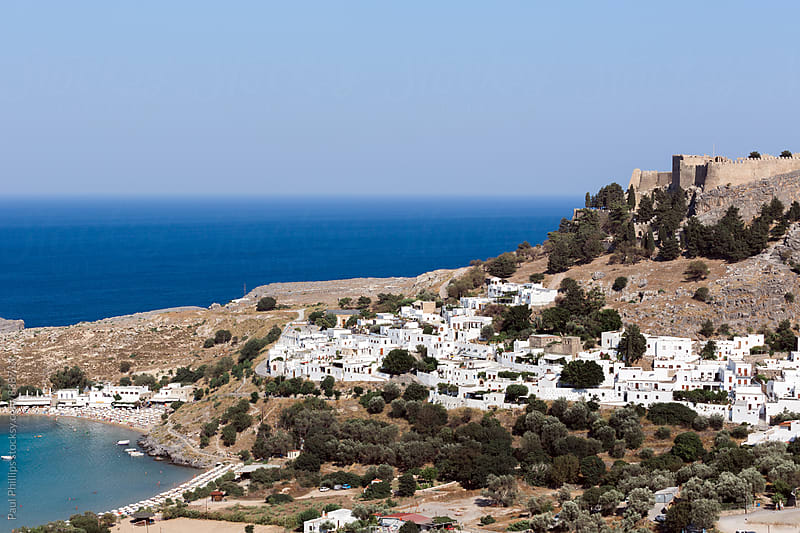 Aerial view of Lindos town and acropolis with the bay and sea behind. by Paul Phillips for Stocksy United