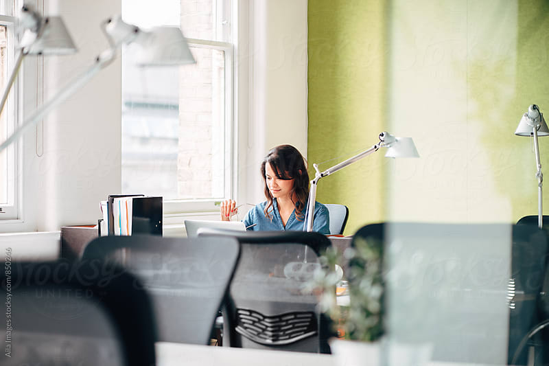 Businesswoman working weekends alone in office on laptop by Aila Images for Stocksy United