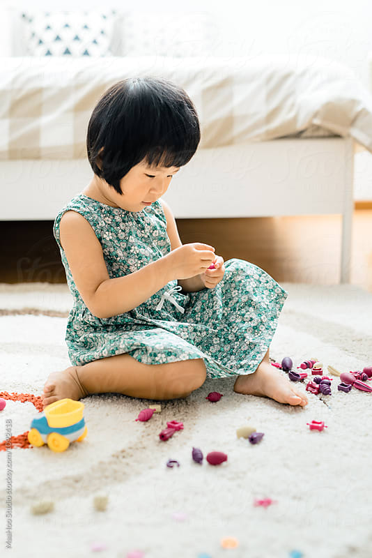 Cute toddler girl playing toys at home by Maa Hoo for Stocksy United