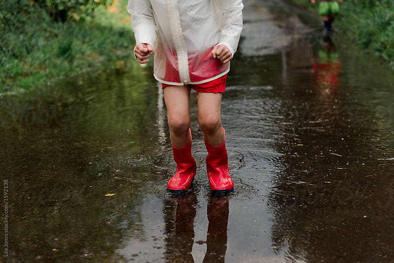 little girl jumping in puddles after the rain