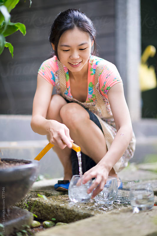 Girl washing glasses on the ground