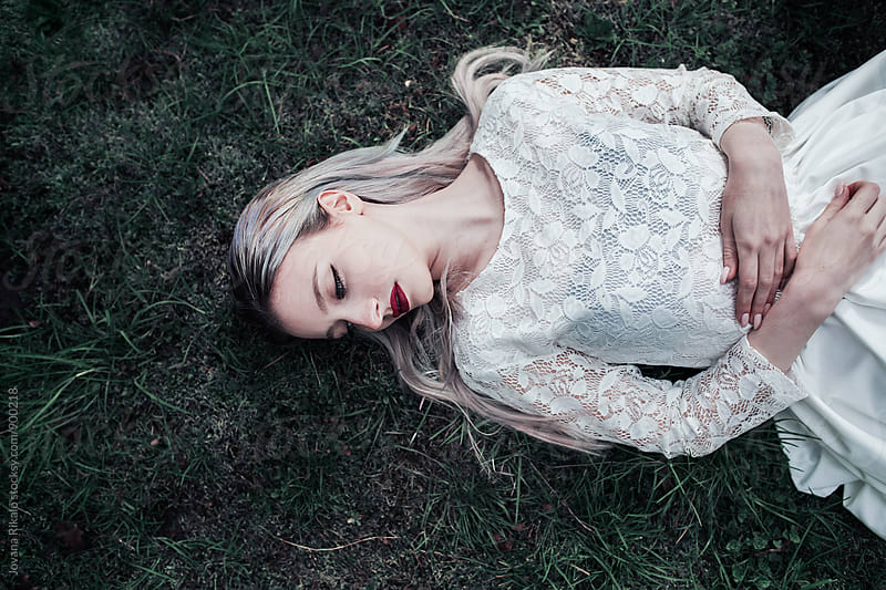 Dreamy portrait of a young woman lying on grass by Jovana Rikalo for Stocksy United