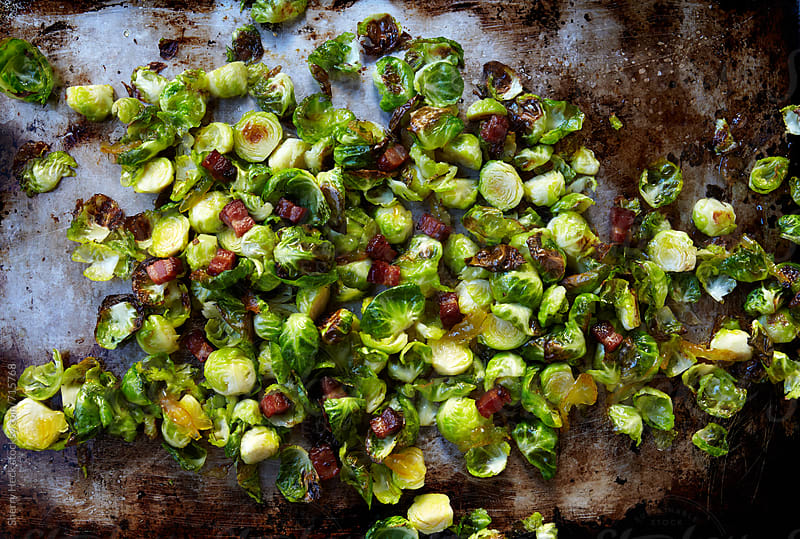 Brussels sprouts and bacon or pancetta roasting on a sheet pan by Sherry Heck for Stocksy United
