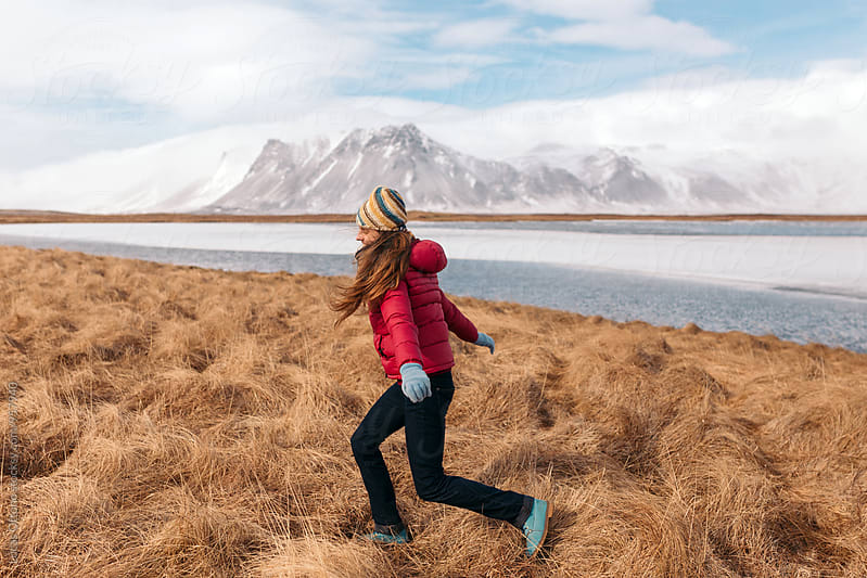 Happy woman running through a winter landscape by Lucas Ottone for Stocksy United
