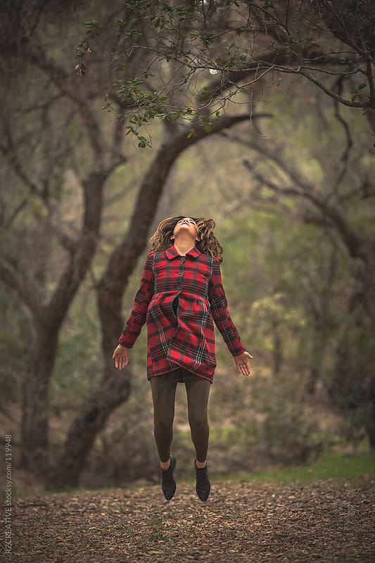 A woman wearing a red plaid coat levitates above the ground. by RZ CREATIVE for Stocksy United
