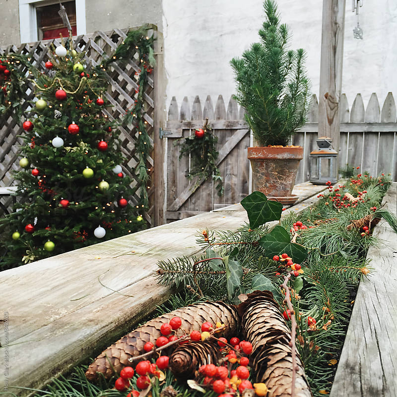 Natural Christmas decorations on a back deck  by Holly Clark for Stocksy United