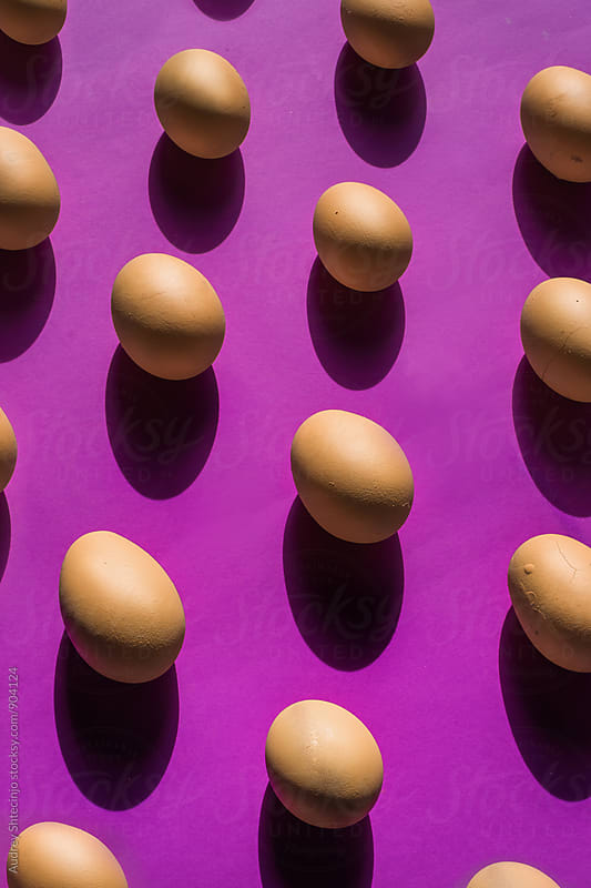 Well arranged raw/hardboiled eggs on purple background. by Marko Milanovic for Stocksy United