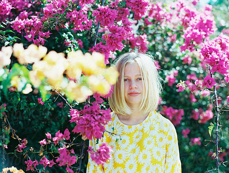 portrait of blonde girl with bob in front of pink bougainvillea by wendy laurel for Stocksy United
