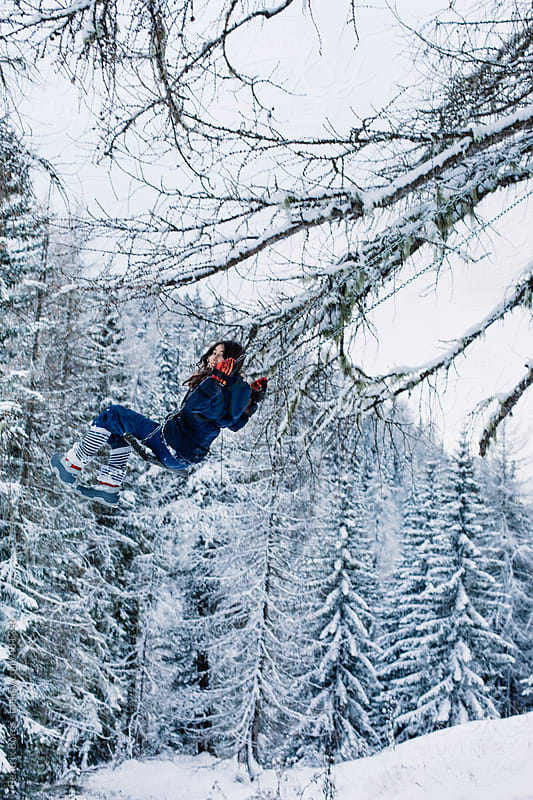 Vertical image of a preteenager girl on a swing in the Winter by Beatrix Boros for Stocksy United