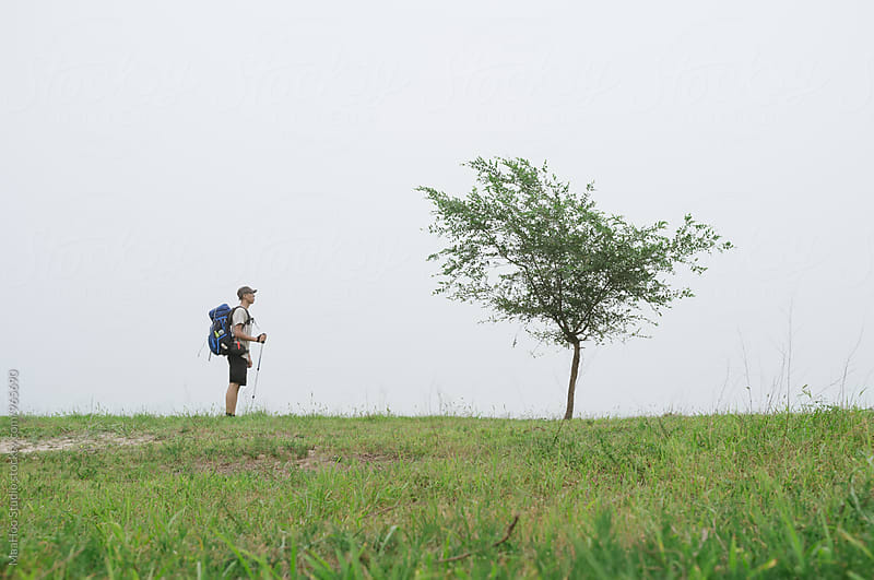 A Chinese young man hiking on grassland and looking  at a tree,Beijing,China by MaaHoo Studio for Stocksy United