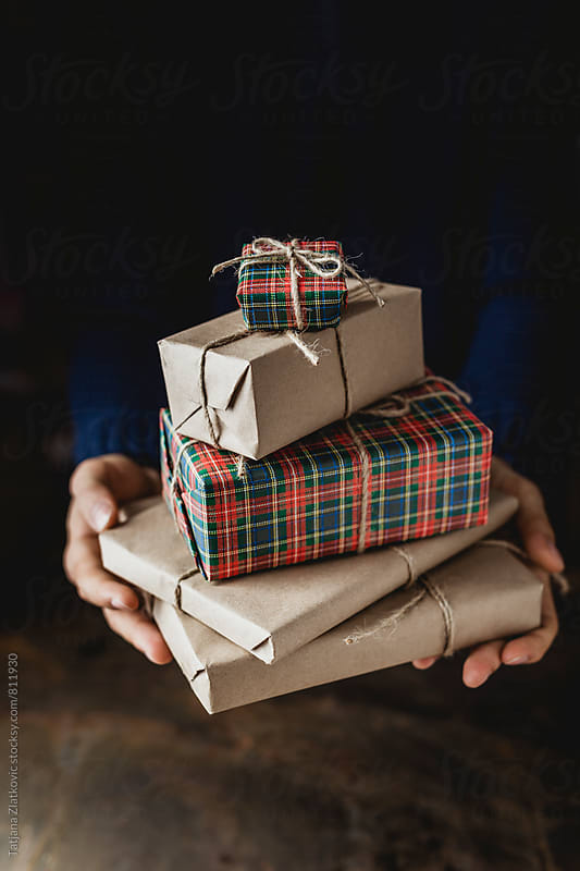 Man holding Christmas gifts by Tatjana Zlatkovic for Stocksy United