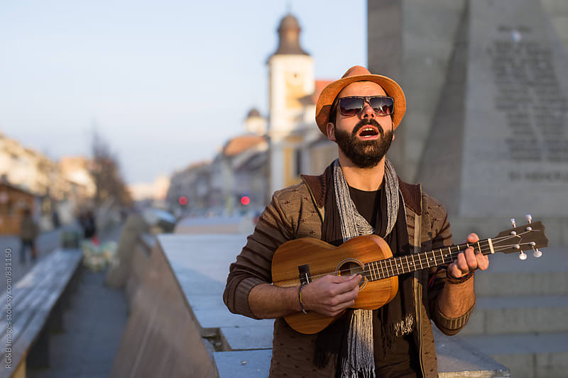 Young man playing music on the city streets by RG&B Images for Stocksy United