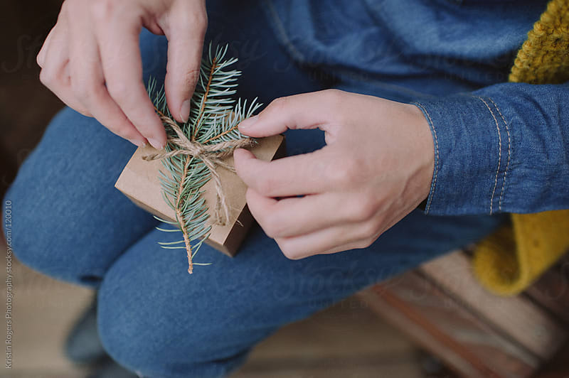 Woman decorating gift with twine and pine by Kristin Rogers Photography for Stocksy United