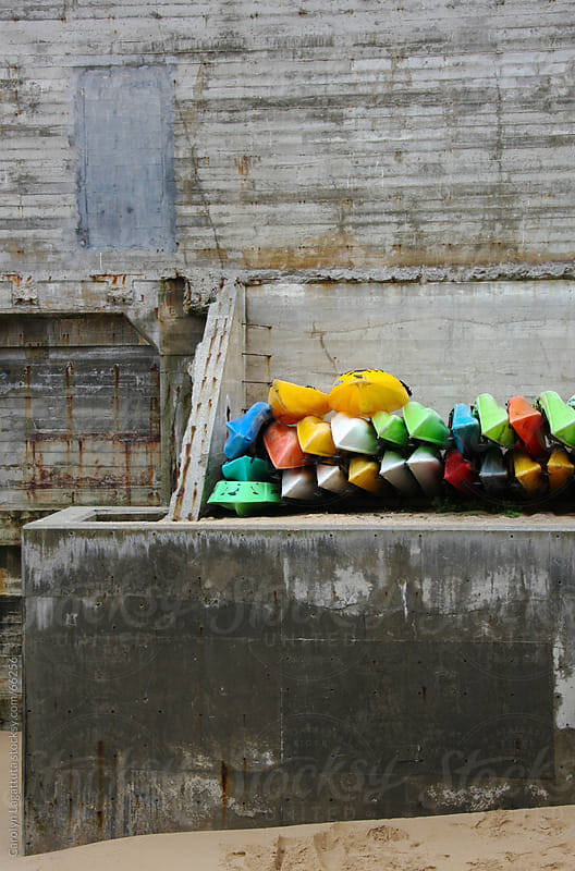 Colorful kayaks stacked up on the beach  by Carolyn Lagattuta for Stocksy United