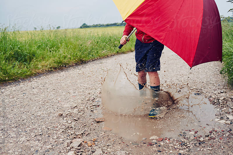 Child having fun playing outdoors on a rainy day with an umbrella by sally anscombe for Stocksy United