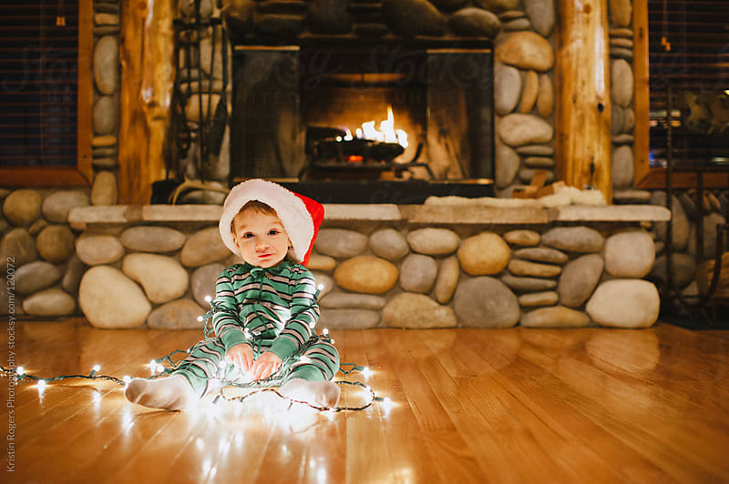 Toddler boy sitting in Christmas lights and Santa hat near fireplace by Kristin Rogers Photography for Stocksy United
